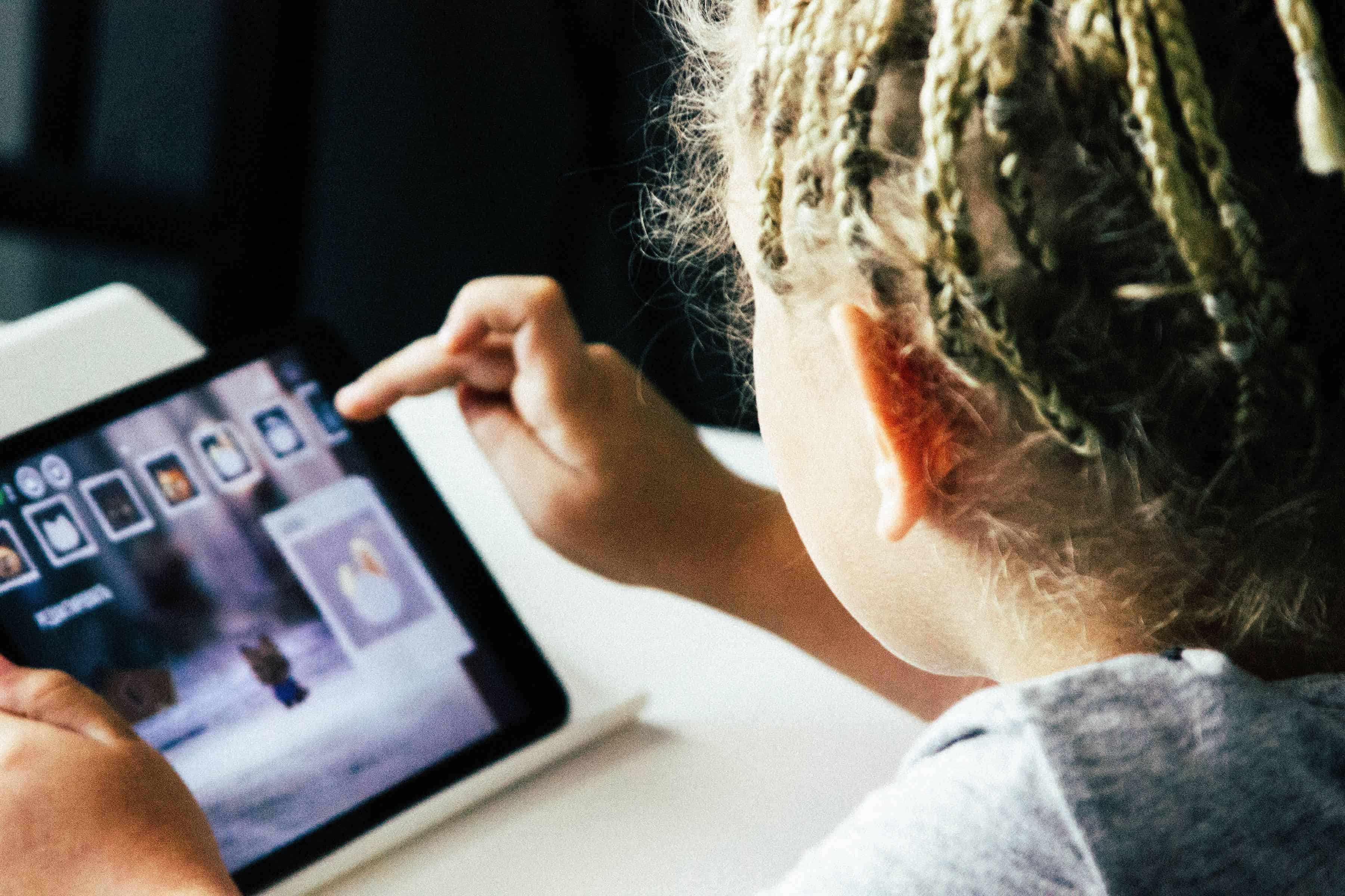 a girl is playing with her tablet.