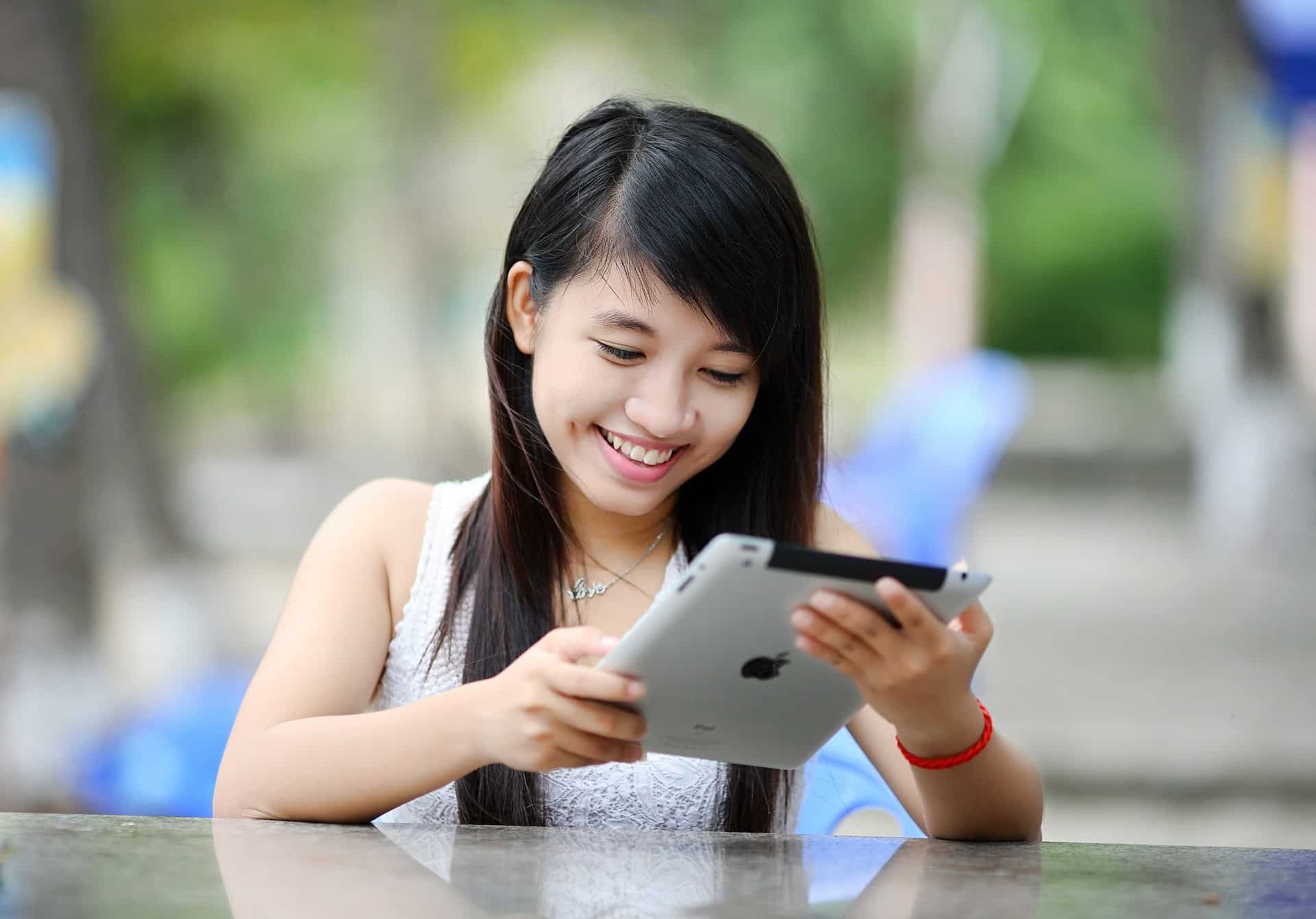 A girl who smile happily, is playing with her ipad.